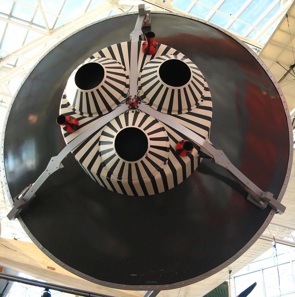 Pohled na zadní část repliky kabiny Mercury. Zřetelný je pruhovaný svazek brzdících raket, které jsou drženy na místě třemi pásy. Právě tyto pásy měly Johnu Glennovi zachránit život.