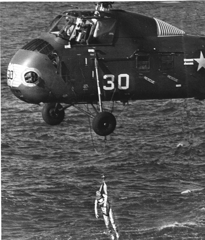 """Záložní vrtulník vytahuje Grissoma z vody. Všimněte si záchranné smyčky, nazývané také """"chomout"""" (horse collar), kterou má Grissom nasazenu obráceně."""