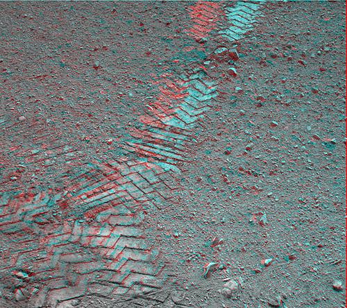 Stopy kol zanechané vozítkem Curiosity v prachu na povrchu Marsu.