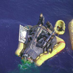 Konečně čerstvý vzduch! Unavená a zklamaná posádka Gemini-VIII, toho času trpící mořskou nemocí, cení zuby pro fotografy. Žabí muži měli také problémy se žaludky, nadýchali se výparů z horkého tepelného štítu Gemini. Okolo kabiny je nafukovací límec, který ji stabilizuje. Až po jeho připevnění bylo možné otevřít poklopy, jinak hrozilo zaplavení kabiny vlnami.