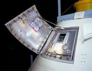 Fotografie poklopu kabiny Apollo Block I. Vnitřní poklop je uzavřen, je zřetelně vidět šest západek, které bylo nutno odšroubovat. Poklop pak bylo třeba vtáhnout dovnitř. Pokud byl tlak v kabině vyšší, než tlak okolí, nebylo jeho otevření myslitelné. Vnější poklop je na fotografii odklopen, chybí třetí poklop, který byl součástí aerodynamického krytu při startu.