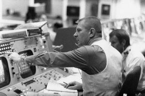 Gene Kranz u své konzoly. Nahoře jsou vidět kontrolky, pomocí kterých s ním komunikovali kontroloři.