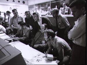 Astronauti, shromáždění kolem jedné z konzol.