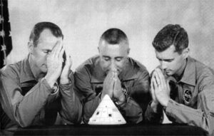 """Žertovný snímek, který od astronautů dostal ředitel kanceláře programu Apollo Joe Shea 19 srpna 1966. Na rubu měl napsáno věnování: """"Ne že bychom Ti nedůvěřovali, Joe, ale tentokrát jsme se rozhodli obrátit na vyšší místa."""" Po 27. lednu 1967 získal napůl žertem pořízený snímek nový temný rozměr…"""