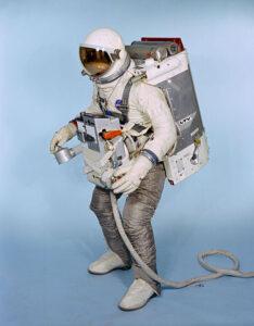 """Skafandr G4C upravený pro misi Gemini-IX (Gemini-IX A). Na hrudi má figurant standardní sestavu ELSS, na zádech pak """"batoh"""" AMU. Všimněte si nohavic skafandru. Ty musely být odolné proti horkým výtokovým plynům z trysek AMU a byly protkány mimo jiné vlákny ze slitiny Chromel-R. Jedna z trysek byla umístěna dokonce tak, že výtokové plyny proudily mezi nohama astronauta! AMU byl skutečně zajímavým strojem…"""