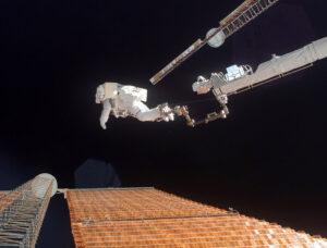 Fotka z října roku 2007 - Scott Parazynski upoutaný na konci robotické paže opravuje solární panel. A jen kousek od tohoto místa se objevily současné problémy.