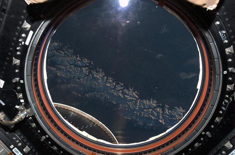 Pohled na Zemi přes kruhové okno modulu Cupola