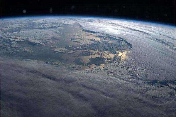 Jde to poznat jen stěží, ale tam mezi mraky se v záři zapadajícího Slunce nachází Dánsko.