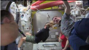 Posádka se zatím shromáždila u hermetického krytu, který odděluje přechodovou komoru od zbytku stanice.