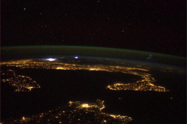 Noční Středozemní moře se vzdálenou bouřkou - povšimněte si hvězdokupy Plejády nad horizontem.