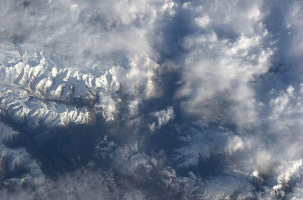 Nad mraky vykukují jen nejvyšší, sněhem zakryté vrcholky hor na Novém Zélandu.