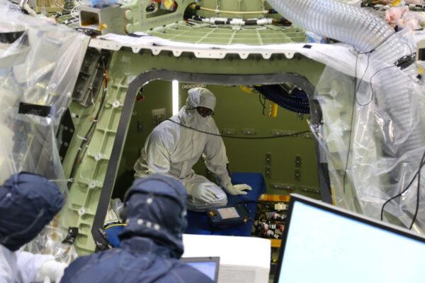 Technik společnosti Lockheed Martin provádí v útrobách lodi Orion první zkoušky elektrických systémů.
