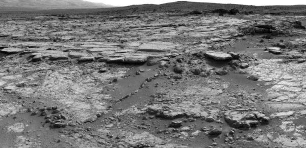 Oblast zvlněných kamenů ve středu fotky dostala jméno Snake River. Snímek pochází z kamer NavCam ze solu 147