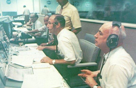 Na obrazovce před Lowem a Gilruthem právě Armstrong a Aldrin vcházejí do historie...