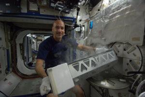 Italský astronaut Luca Parmitano u staniční chladničky MELFI, kde se uchovávají vzorky.