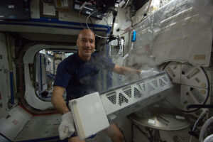 Italský astronaut Luca Parmitano u staniční chladničky MELFI, kde se uchovávaly vzorky.