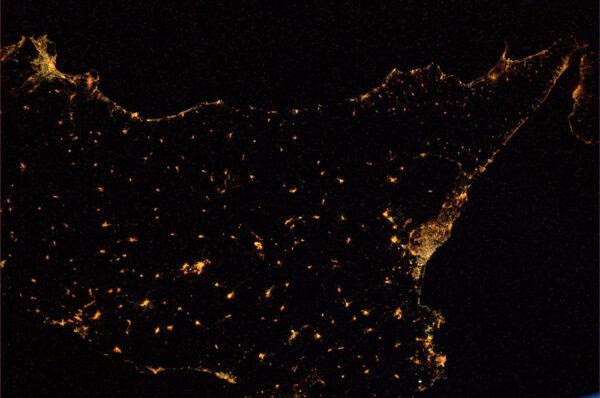 Noční Sicílie. Pokud se dobře podíváte na východní pobřeží ostrova, uvidíte lávu vytékající z Etny.