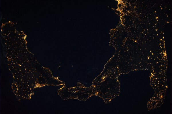 Noční verze předchozího snímku.  Je zde krásně vidět neobydlený kruh okolo Etny, ze které vytéká láva