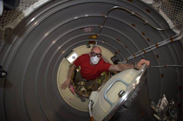 Alexander Gerst vstupuje do útrob lodi ATV. Rouška patří mezi běžné ochranné pomůcky při prvním vstupu do nové lodi - v jejích útrobách může být  zvířený prach, nebo drobné úlomky.Astronauti proto vždy umístí do útrob lodi malou filtrační jednotku, která pročistí vzduch.