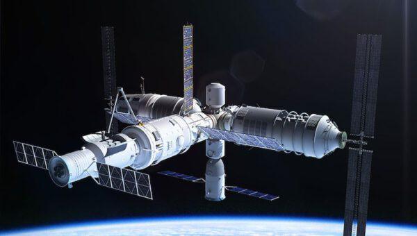Robotické rameno čínské orbitální stanice třetí generace vytahuje náklad z otevřeného nákladového prostoru nehermetické nákladní lodi Tianzhou.