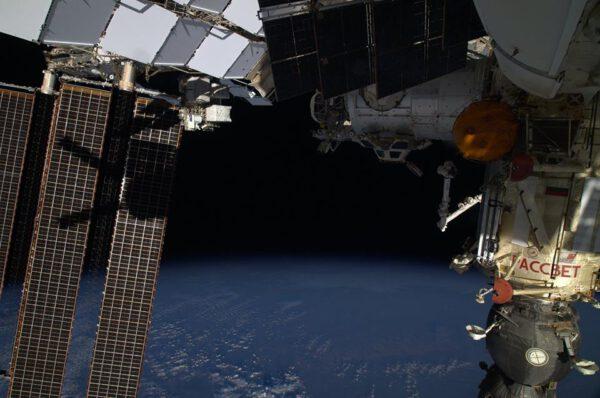 Část Sojuzu TMA-13M, kterým Alex se svými kolegy přiletěl, modul Rassvět, část Zarji, vzdálená Tranquillity a Cupola a stín ATV-5 na solárních panelech stanice.