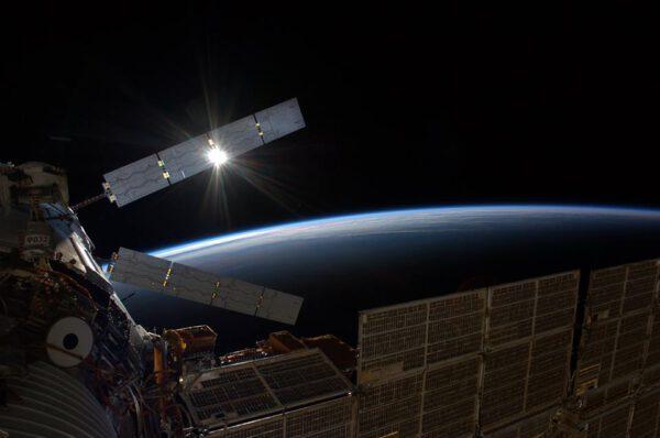 Zapadající Slunce za zásobovací lodí ATV-5. V popředí část servisního modulu Zvězda se solárními panely.