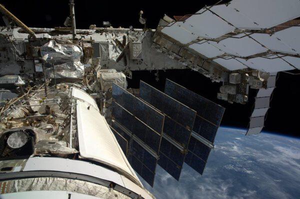 Nezvyklý pohled na ISS z okénka modulu Poisk. Vidět na něm můžeme modul Zarja se složenými solárními panely, kus hlavního nosníku a panely radiátorů, které odvadějí přebytečné teplo.