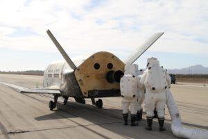 Odborníci v ochranných skafandrech u miniraketoplánu