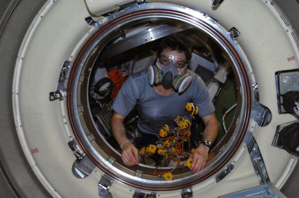 Člen posádky ISS vstupuje do ATV s ochrannými prostředky.