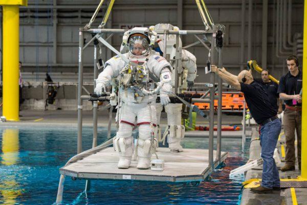 Spouštění astronauta do bazénu.