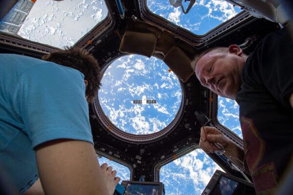 Barry Wilmore a Samantha Cristoforetti sledují z modulu Cupola odlétající loď Dragon.