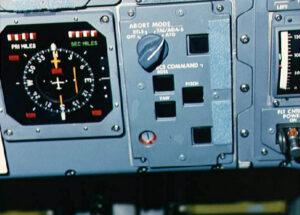 Výmluvná fotografie části palubní desky Challengeru po dosažení orbitu: otočný volič módu abortu a vpravo vedle něj tlačítko potvrzení zvolené volby
