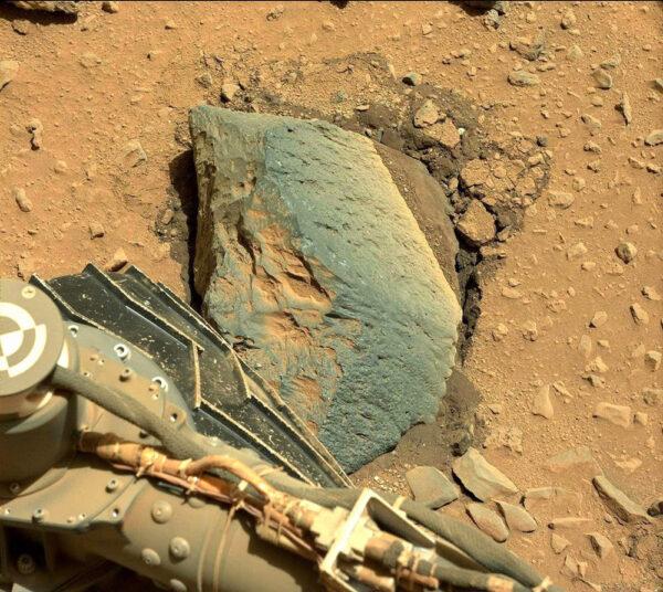 Během solu 403 se Curiosity pokusila vyvrátit kámen, aby mohla prozkoumat jeho podloží, které je vidět na fotce jako tmavší vrstva.