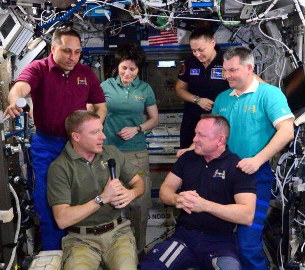 Tady to začalo - Velitel 42. dlouhodobé expedice Barry Wilmore (dole vpravo) předává velení Terry Virtsovi (s mikrofonem), který je hlavou 43. expedice na ISS.