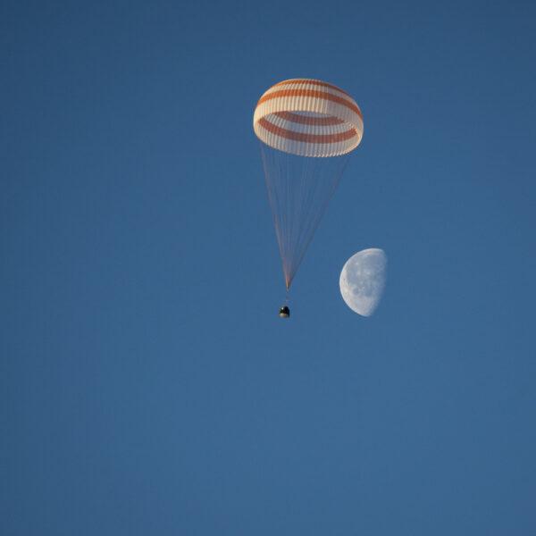 Povedený snímek zachycující klesající Sojuz a ubývající Měsíc.
