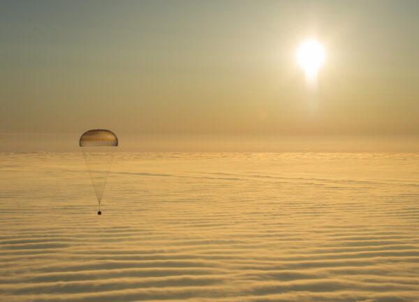 Mimořádně působivá fotka - Klesající Sojuz na padáku, mraky a Slunce.