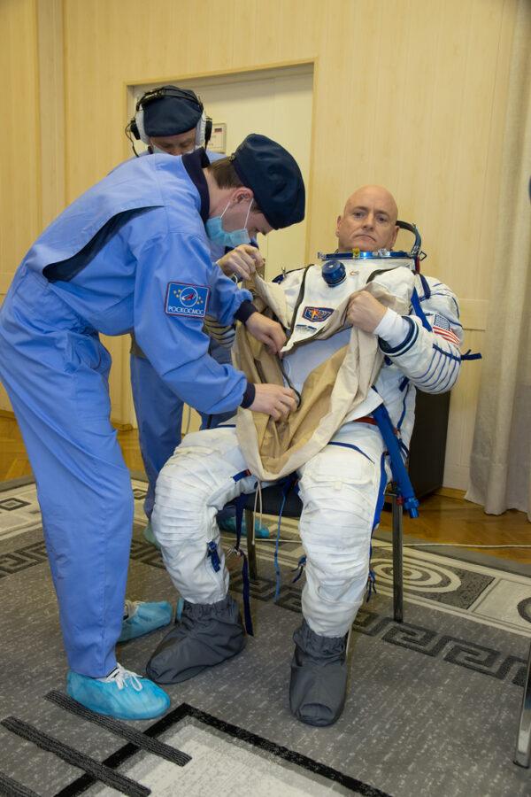 Scott Kelly při zkušebním oblékání skafandru Sokol, který se používá při startech a přistáních.