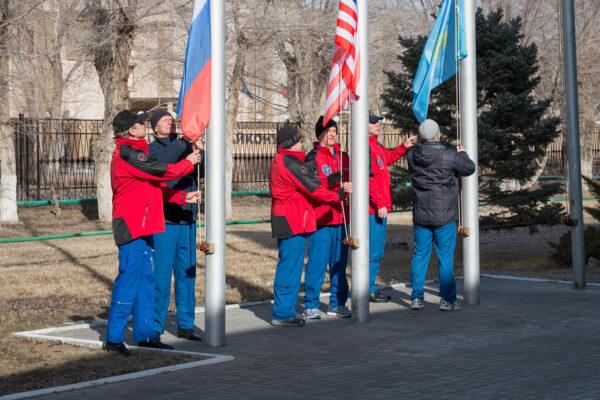 Vytahování ruské, americké a kazašské vlajky