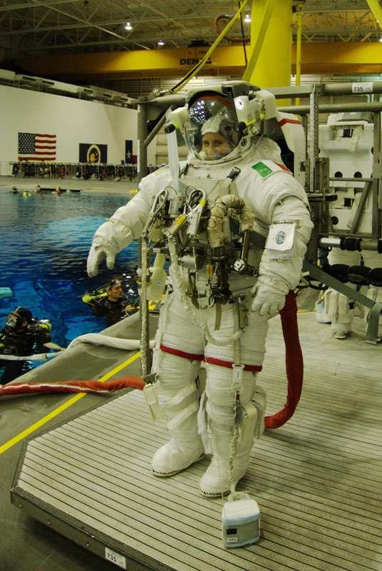 Jsem připravená na spuštění do bazénu v NBL. Všimněte si navijáku s 26 metrů dlouhým bezpečnostním lankem, který leží na zemi. Velká karabina, kterou mám na břiše se ihned po opuštění přechodové komory musí připojit ke konstrukci stanice zatímco naviják bude putovat se mnou.