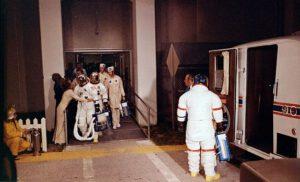 """Posádka Apolla 17 při přesunu na rampu: Cernan čeká u """"astrovanu"""", Evans se loučí se ženou a Schmitt se šklebí v pozadí"""