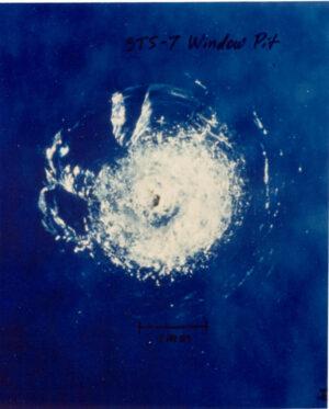 Tabulka skla z Challengeru, poškozená miniaturní částečkou laku
