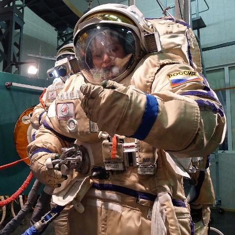Používám levé zrcátko, abych připojila kyslíkové a další vedení ke skafandru.