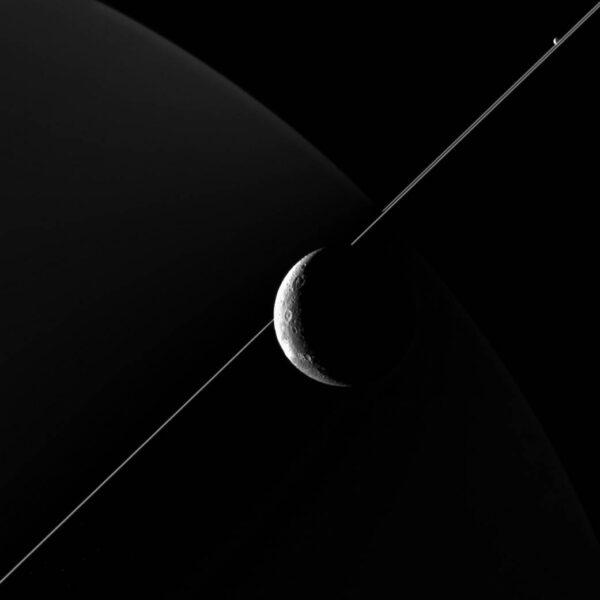 Na tomto snímku můžeme vidět i saturnův měsíc Enceladus - vpravo nahoře. Snímekbyl pořízen ve vzdálenosti 77 000 km od povrchu Dione. Rozlišení snímku je 5 km/pixel.