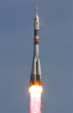 Raketa Sojuz se stejnojmennou lodí schovanou pod aerodynamickým krytem. Urychlovací bloky po stranách obklopují centrální stupeň. Pod oranžovým krytem ve střední části se schovávají motory 2. stupně.