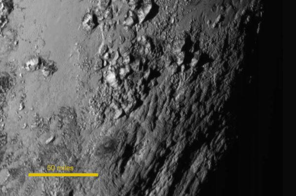 Snímek Pluta z kamery LORRI pořízený zhruba 90 minut před maximálním přiblížením. Hory jsou zřejmě tvořeny ledem.