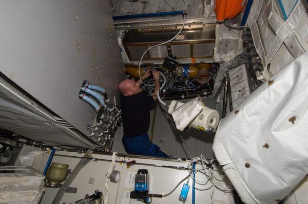 André Kupiers používá vysavač k vyčištění ventilačního systému Columba.