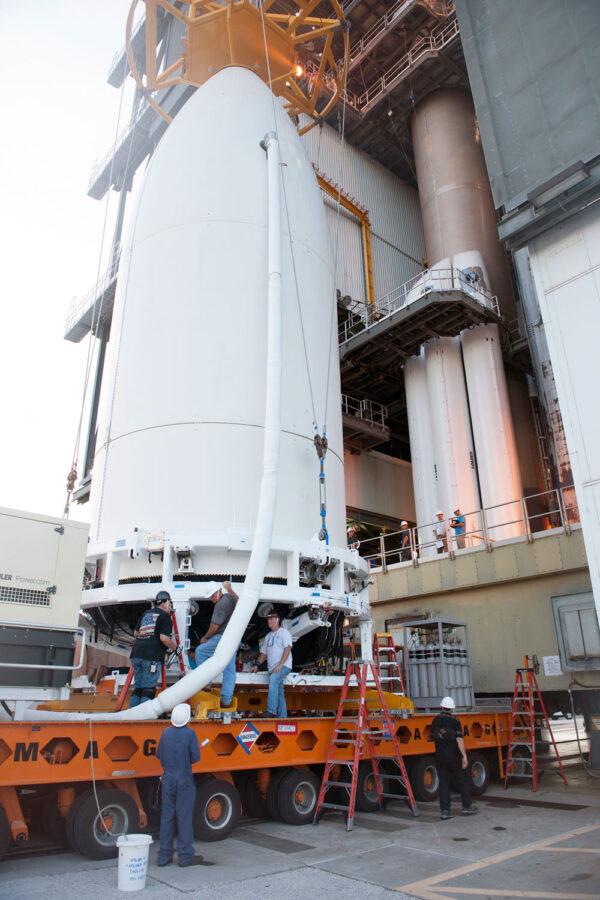 Aerodynamický kryt s družicí přivezl k montážní věži mnohakolový transportér. Všimněte si zároveň velikosti celého krytu ve srovnání s lidskou postavou.