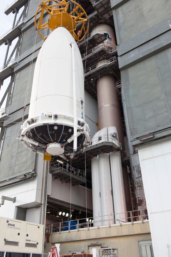 Zvedání aerodynamického krytu - v pozadí vidíme raketu Atlas V s urychlovacími bloky na tuhá paliva.