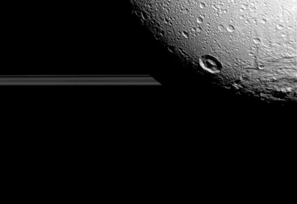 Měsíc Dione - v pozadí pak vidíme saturnovy prstence