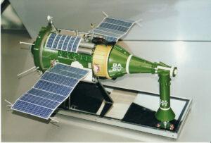 Model lodi TKS. Vlevo od žluté části se nachází blok FGB zajišťující manévrování a pohodlí posádky. Vpravo se nachází loď VA rozdělena na 3 části. Návratový modul je nejširší kónická část nejblíže FGB, která může vydžet v samostaatném letu několik dní a poté snížit svojí oběžnou dráhu za pomocí raket na přední části. Při havárii nosné rakety bylo možné využít záchrannou věžičku. Ta leží na podstvci vpravo. Zdroj: upload.wikimedia.org